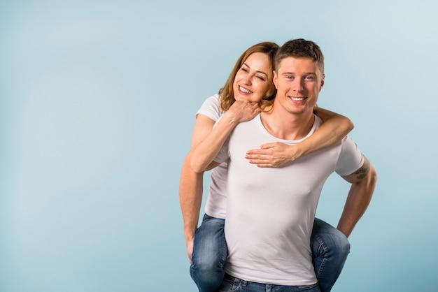 Glimlachende jonge mens die op de rug rit geeft aan haar meisje tegen blauwe achtergrond