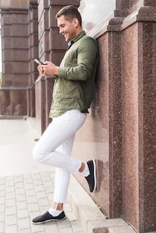 Glimlachende jonge mens die op muur leunt die cellphone gebruikt