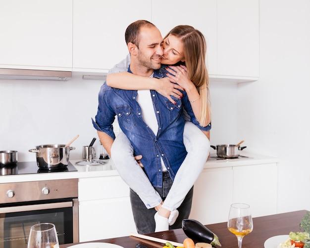 Glimlachende jonge mens die pret hebben en op de rug rit geven aan zijn blije vrouw in de keuken