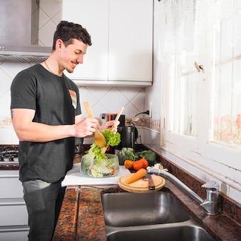 Glimlachende jonge mens die salade voorbereiden dichtbij de keukengootsteen