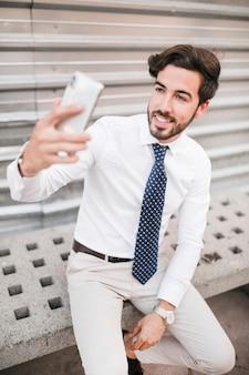 Glimlachende jonge mens die selfie met mobiele telefoon nemen