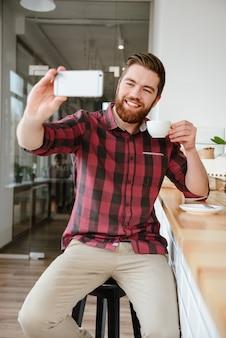 Glimlachende jonge mens die selfie nemen en kop van koffie houden
