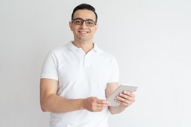 Glimlachende jonge mens die tabletcomputer met behulp van
