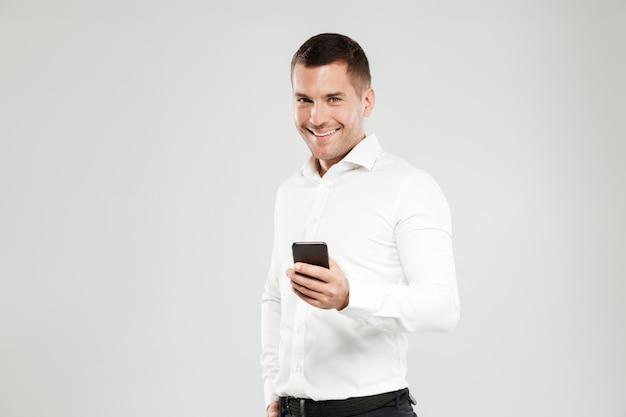 Glimlachende jonge mens die telefonisch babbelt.