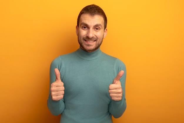 Glimlachende jonge mens die voorzijde bekijkt die duimen toont die omhoog op oranje muur wordt geïsoleerd
