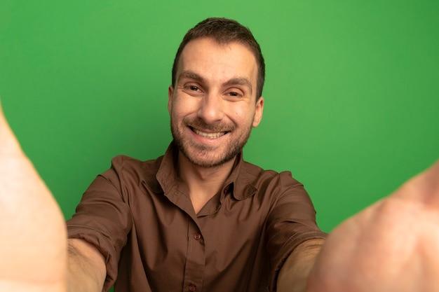 Glimlachende jonge mens die voorzijde bekijkt die uit handen naar camera kijkt die op groene muur wordt geïsoleerd