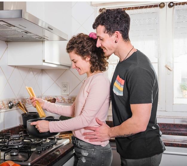 Glimlachende jonge mens die zich achter haar vrouw bevindt die spaghetti thuis voorbereidt