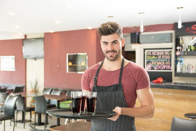 Glimlachende jonge mens het dienen glazen dranken in het restaurant