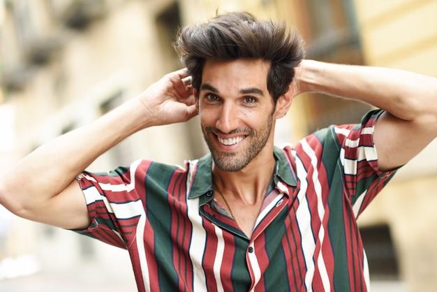 Glimlachende jonge mens met donker haar en modern kapsel die vrijetijdskleding in openlucht dragen