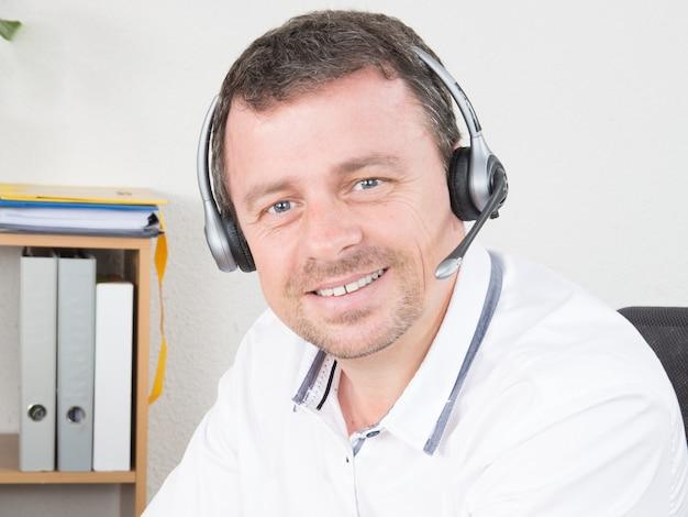Glimlachende jonge mens met hoofdtelefoon die in call centre werkt