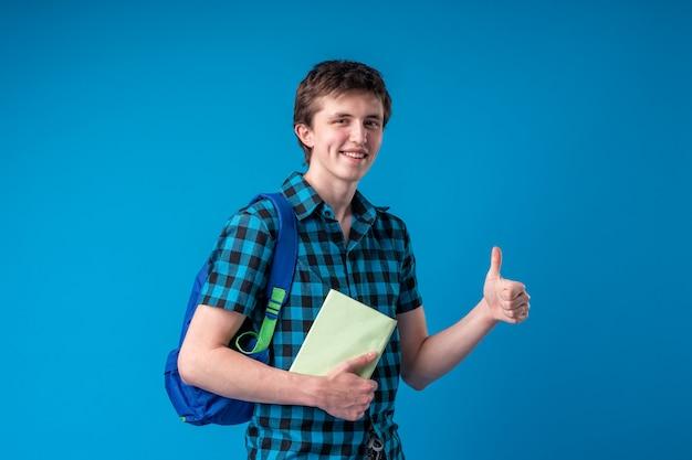 Glimlachende jonge mensenstudent in vrijetijdskleding met de boeken van een rugzakholding