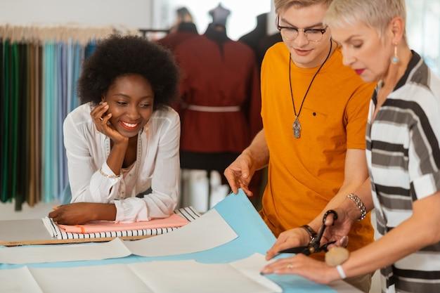 Glimlachende jonge modeontwerper die op de tafel leunt terwijl ze naar haar collega's kijkt