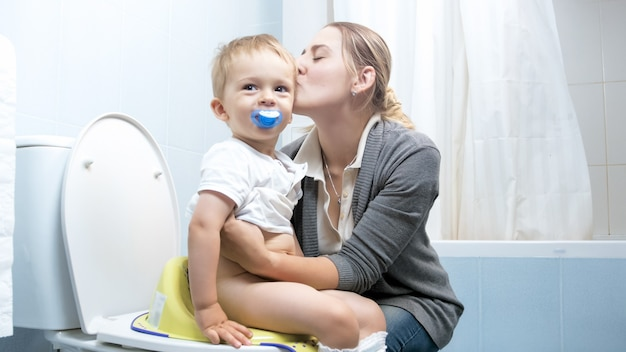 Glimlachende jonge moeder die haar peuterzoon onderwijst die volwassen toilet gebruikt.