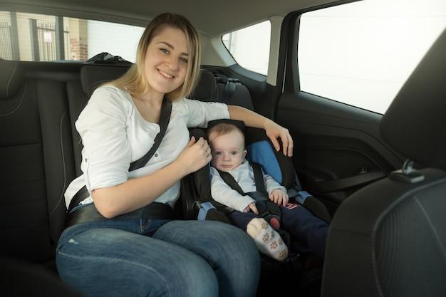 Glimlachende jonge moeder en babyjongen in autoveiligheidszitje