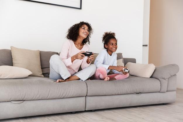 Glimlachende jonge moeder en haar dochtertje in pyjama ontspannen op een bank, videogames spelend