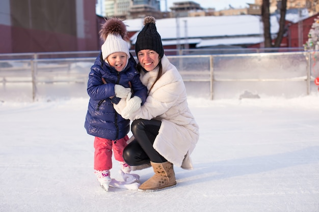 Glimlachende jonge moeder en haar schattige kleine dochter die samen schaatsen