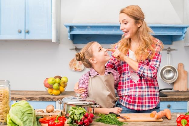 Glimlachende jonge moeder wat betreft de neus van haar dochter met vinger in de keuken