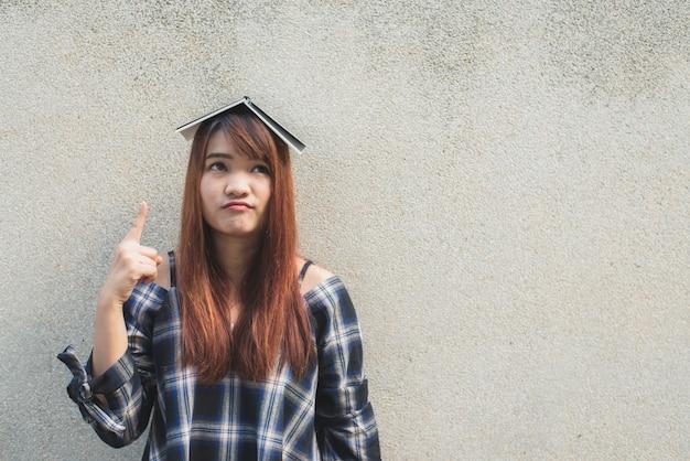 Glimlachende jonge mooie aziatische vrouw denken met een boek over hoofd op betonnen muur achtergrond. vintage effect stijl foto's.