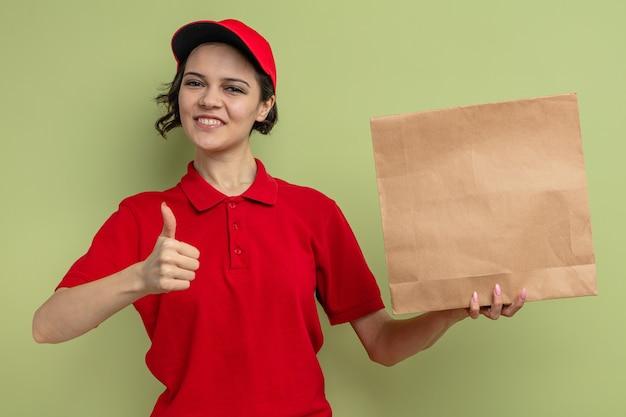 Glimlachende jonge mooie bezorger die papieren voedselverpakkingen vasthoudt en omhoog steekt