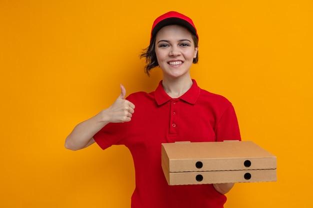 Glimlachende jonge mooie bezorger die pizzadozen vasthoudt en omhoog steekt