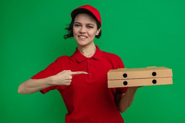 Glimlachende jonge mooie bezorger die pizzadozen vasthoudt en wijst