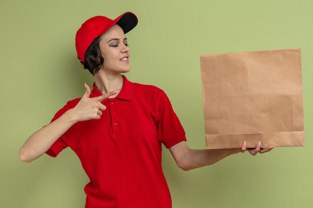 Glimlachende jonge mooie bezorger die vasthoudt en wijst naar papieren voedselverpakkingen