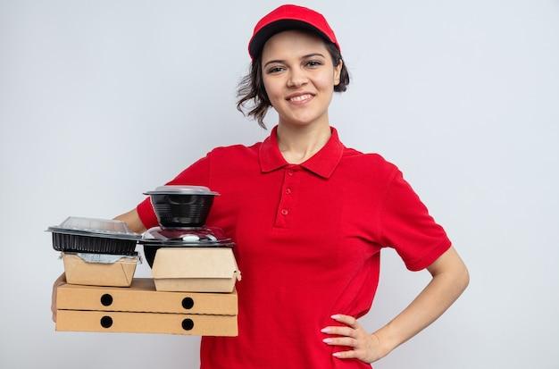 Glimlachende jonge mooie bezorger die voedselcontainers en verpakkingen op pizzadozen vasthoudt