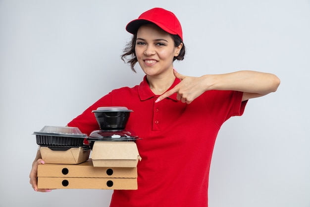 Glimlachende jonge, mooie bezorger die voedselcontainers vasthoudt en wijst met verpakking op pizzadozen