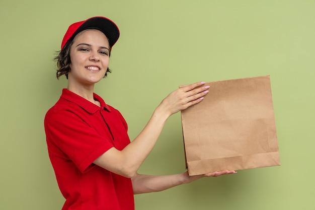 Glimlachende jonge mooie bezorger houdt papieren voedselverpakking vast