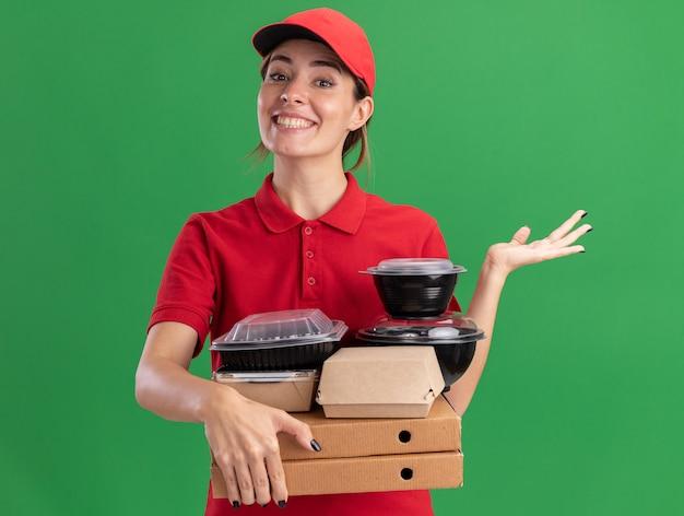 Glimlachende jonge mooie bezorger in uniform houdt papieren voedselpakketten en containers op pizzadozen en houdt de hand open geïsoleerd op groene muur