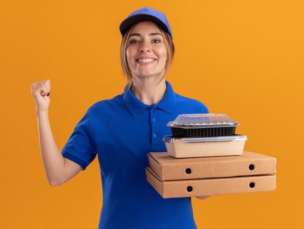 Glimlachende jonge mooie bezorger in uniform wijst naar achteren en houdt papieren voedselpakketten en containers op pizzadozen die op oranje muur worden geïsoleerd