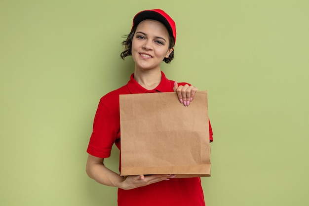 Glimlachende jonge mooie bezorger met papieren voedselverpakkingen