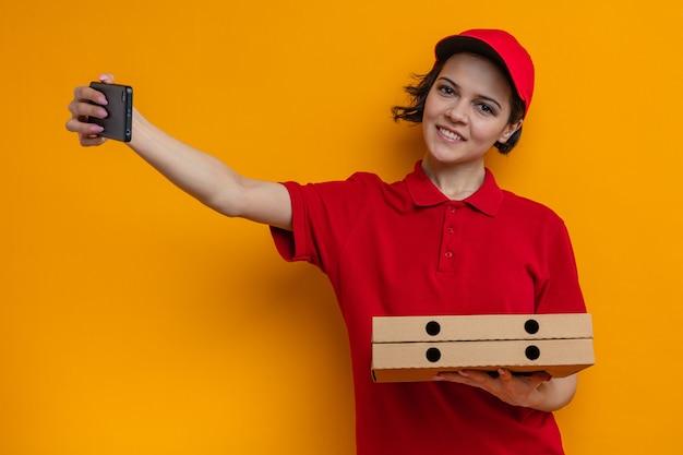 Glimlachende jonge mooie bezorger met pizzadozen en telefoon