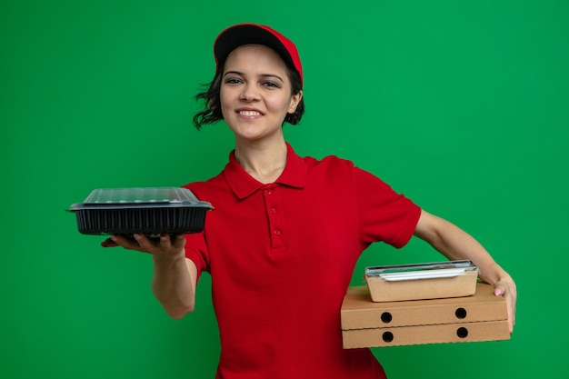 Glimlachende jonge mooie bezorger met voedselcontainer en verpakking op pizzadozen