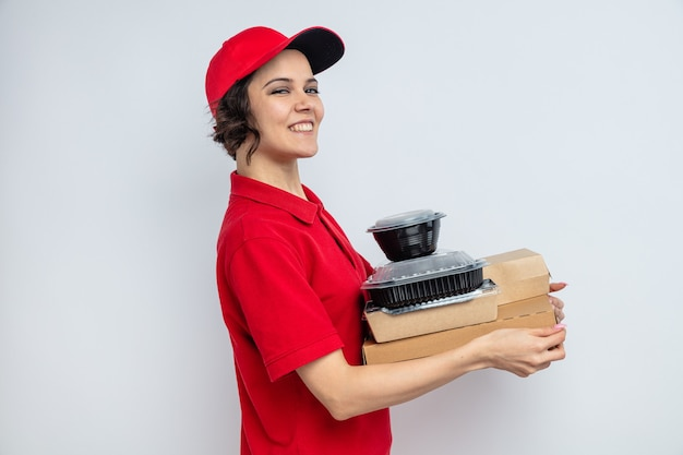 Glimlachende jonge mooie bezorger staat zijwaarts met voedselcontainers en verpakkingen op pizzadozen