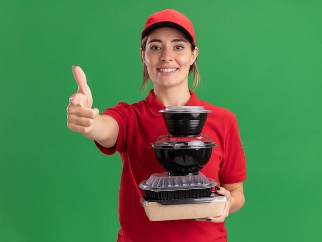 Glimlachende jonge mooie bezorgvrouw in uniform duimen die voedselcontainers op voedselpakket houden dat op groene muur wordt geïsoleerd