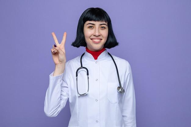 Glimlachende jonge mooie blanke vrouw in doktersuniform met stethoscoop gebaren overwinningsteken