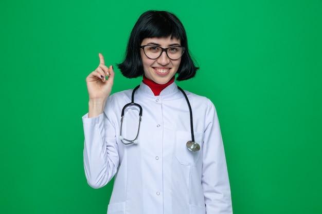 Glimlachende jonge, mooie blanke vrouw met een bril in doktersuniform met een stethoscoop die naar boven wijst