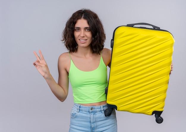 Glimlachende jonge mooie de holdingskoffer van de reizigersvrouw en het doen van vredesteken op geïsoleerde witte muur