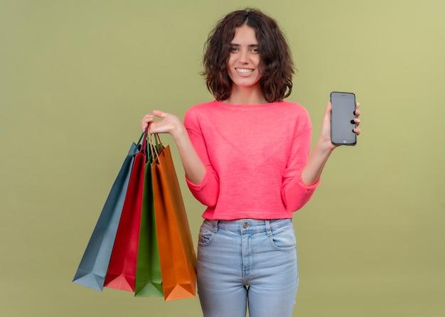 Glimlachende jonge mooie het kartonzakken van de vrouwenholding en mobiele telefoon op geïsoleerde groene muur
