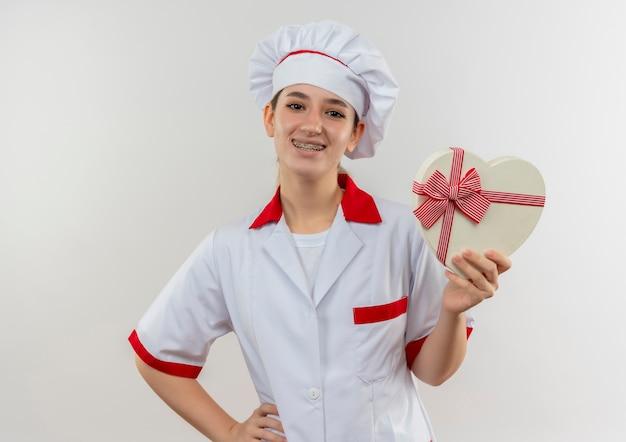 Glimlachende jonge mooie kok in eenvormige chef-kok met tandsteunen die hartvormige giftdoos met hand op taille houden die op witte ruimte wordt geïsoleerd