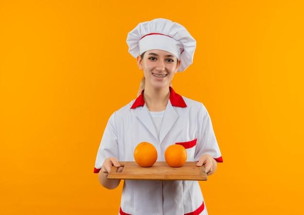 Glimlachende jonge mooie kok in eenvormige chef-kok met tandsteunen die snijplank met sinaasappelen erop houden die op oranje ruimte wordt geïsoleerd