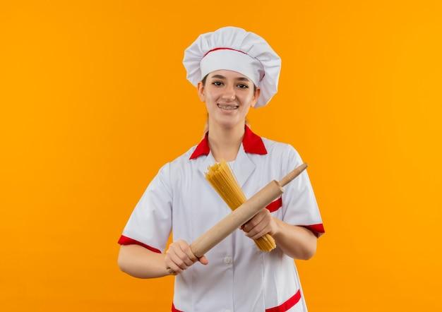 Glimlachende jonge mooie kok in eenvormige chef-kok met tandsteunen die spaghettideegwaren en deegroller houden die op oranje ruimte wordt geïsoleerd