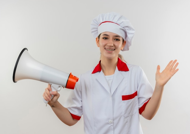 Glimlachende jonge mooie kok in eenvormige chef-kok met tandsteunen die spreker houden en lege hand tonen die op witte ruimte wordt geïsoleerd