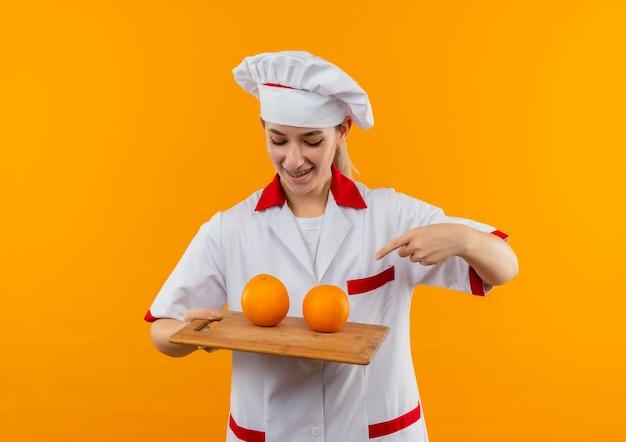 Glimlachende jonge mooie kok in uniform chef-kok met beugels houden kijken en wijzend op snijplank met sinaasappelen erop geïsoleerd op oranje ruimte