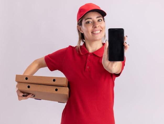 Glimlachende jonge mooie leveringsvrouw in de eenvormige dozen van de holdingspizza en telefoon die op witte muur wordt geïsoleerd