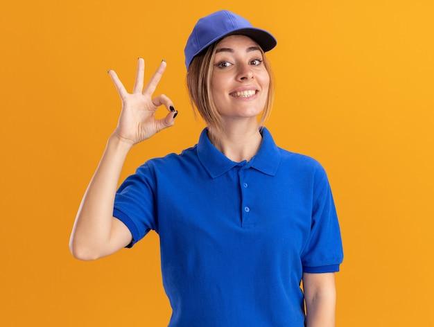 Glimlachende jonge mooie leveringsvrouw in eenvormige gebaren ok handteken dat op oranje muur wordt geïsoleerd
