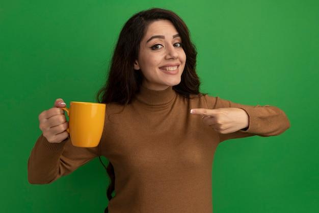 Glimlachende jonge mooie meisjesholding en punten bij kop thee die op groene muur wordt geïsoleerd