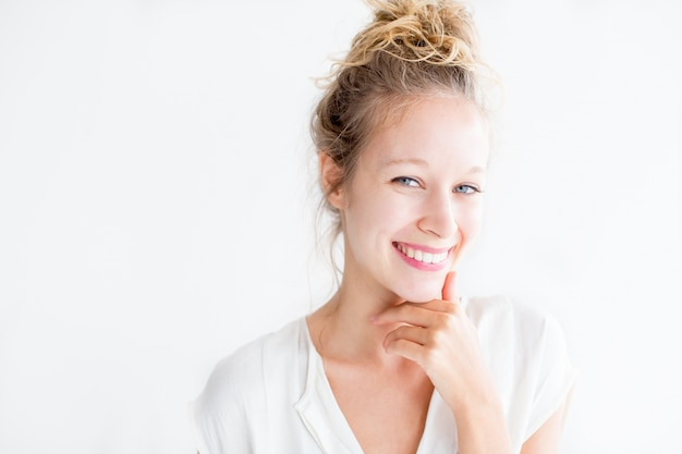 Glimlachende jonge mooie vrouw aan de kin aanraken