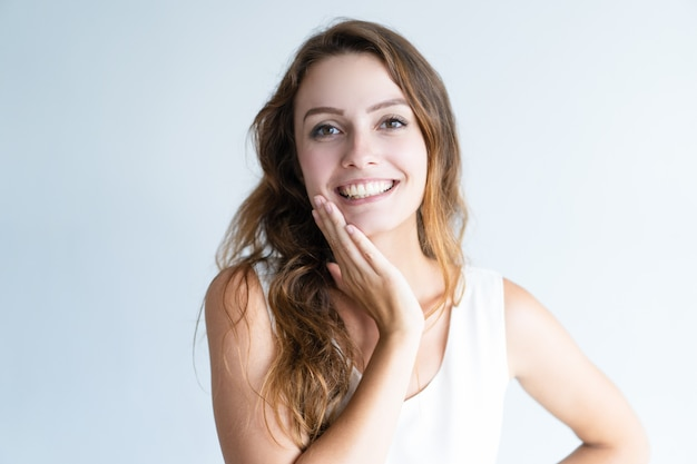 Glimlachende jonge mooie vrouw die camera en wat betreft gezicht bekijkt